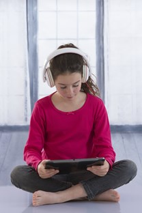 Student sitting on the floor wearing headphones and reading from a tablet computer.